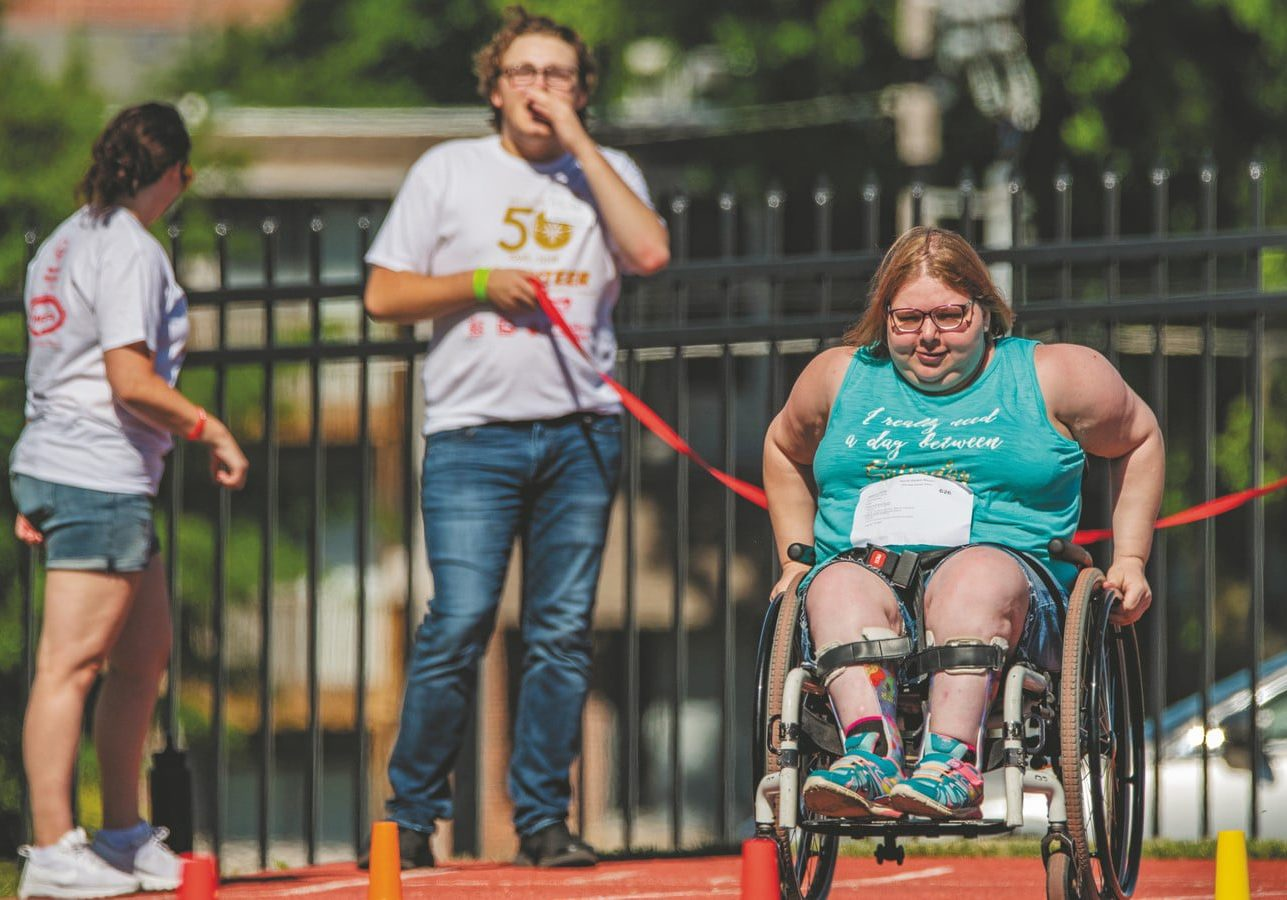An athlete who uses a wheelchair races down the track while a volunteer looks on from behind