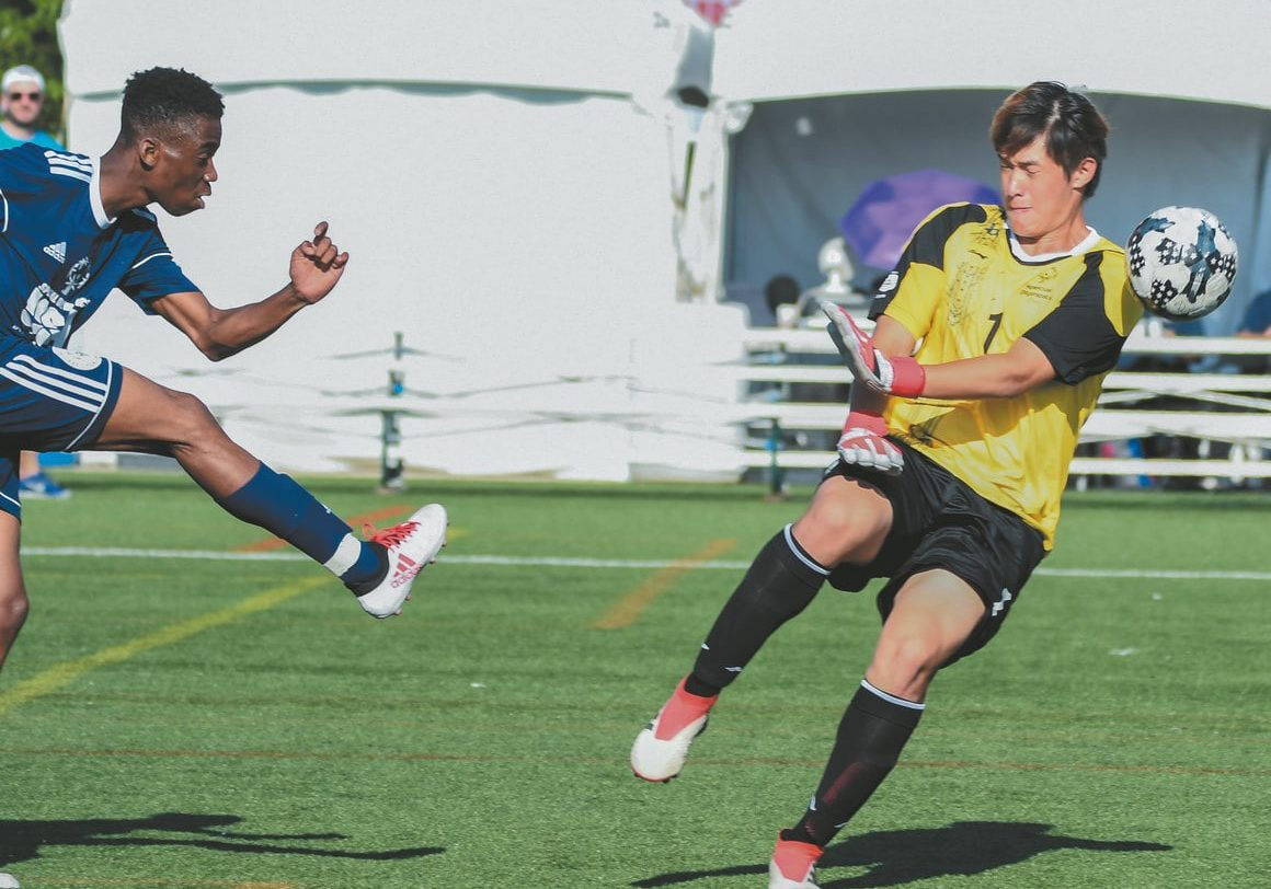 A soccer athlete follows through after kicking the ball as it sails past the goalkeeper