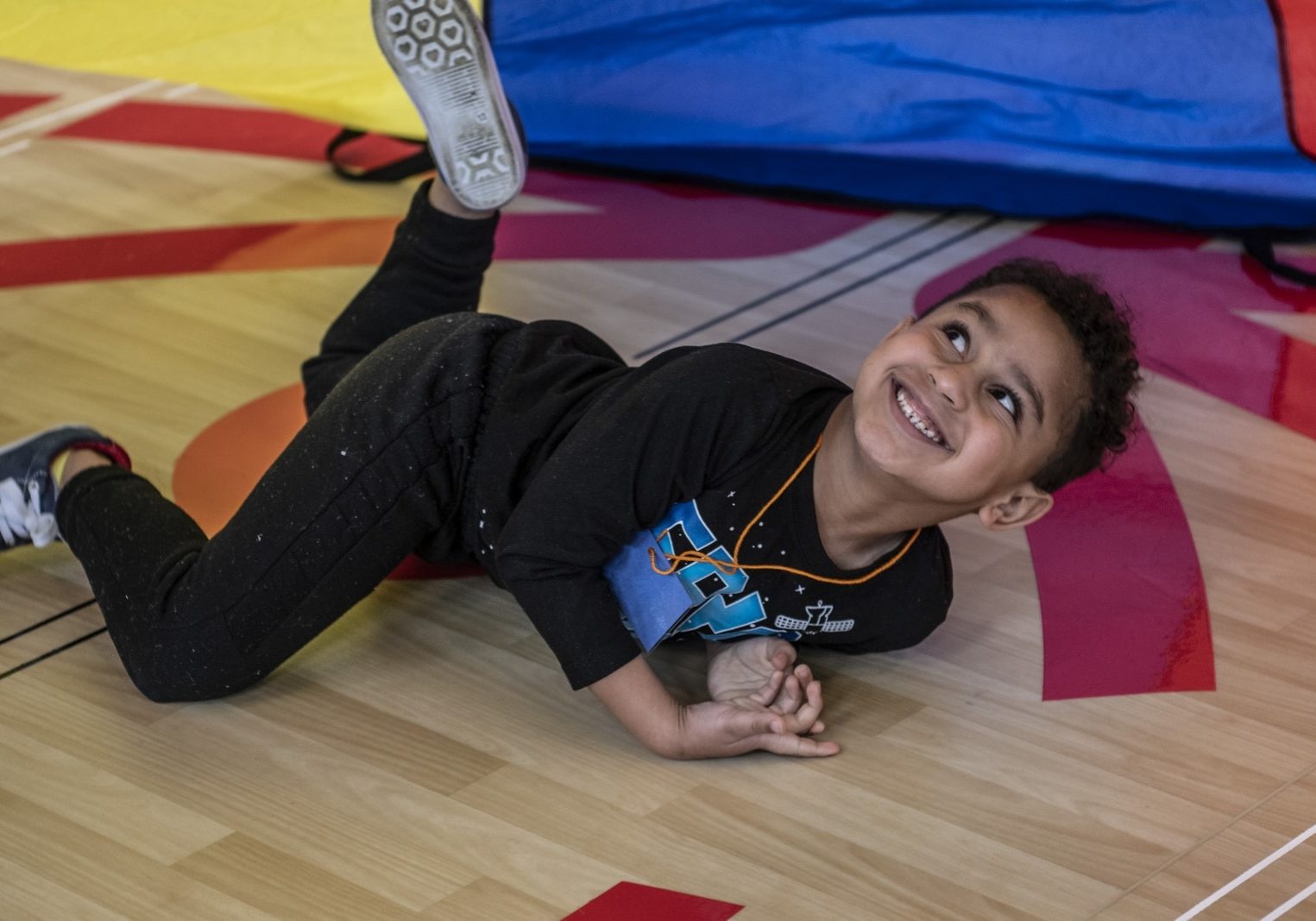 Young athlete laying on belly under a parachute and looking up while smiling