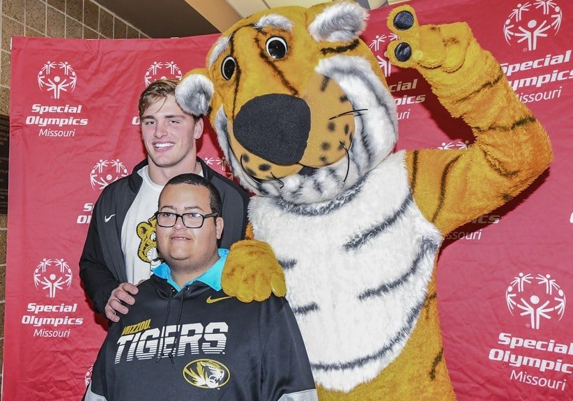 An athlete, a volunteer, and someone in a Truman the Tiger costume pose for a photo