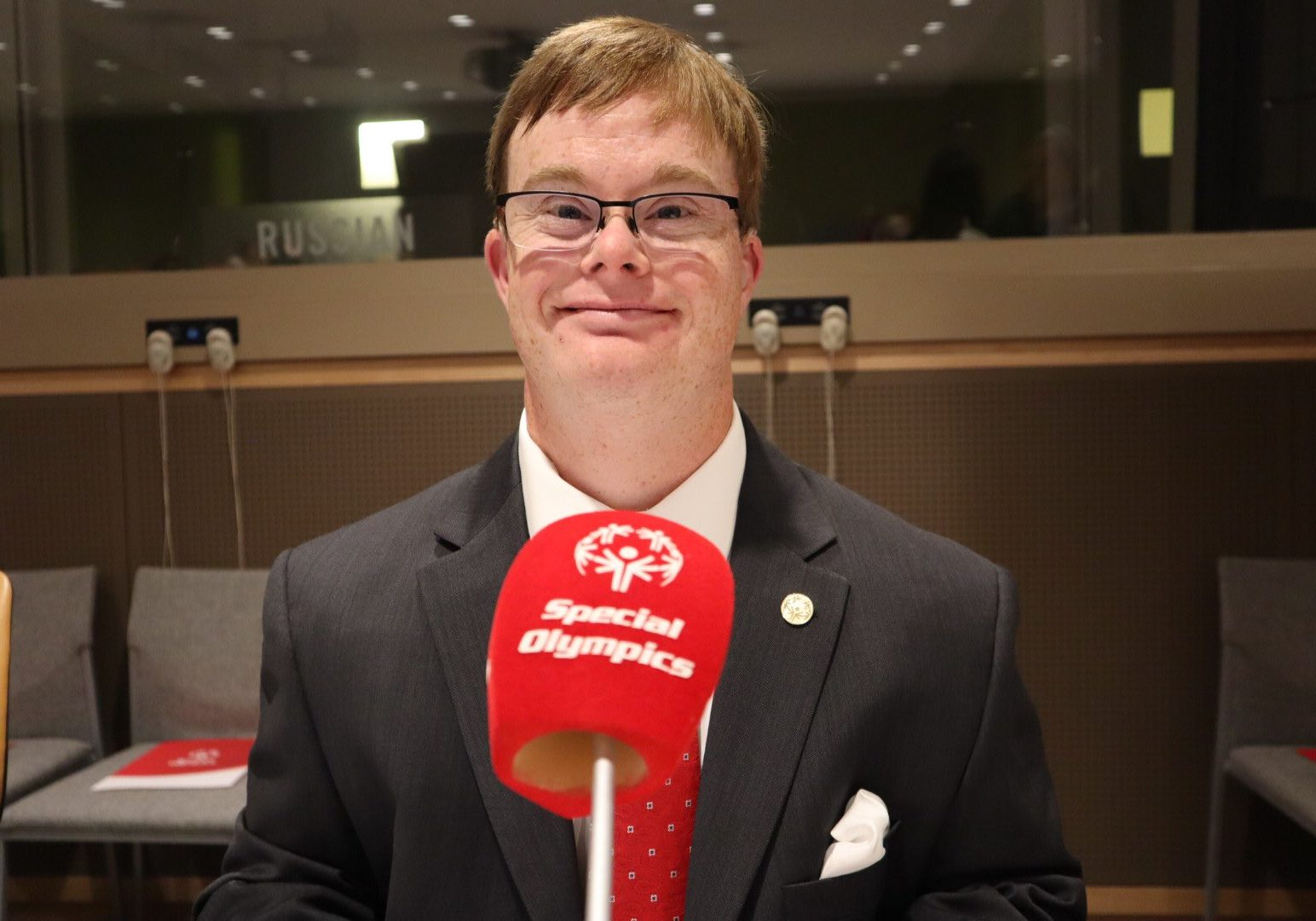 Athlete smiles at camera with a red microphone in front of them