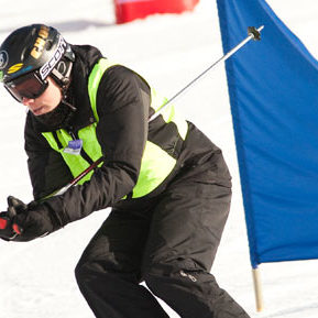 An athlete dressed in black skis down a hill past a blue marker