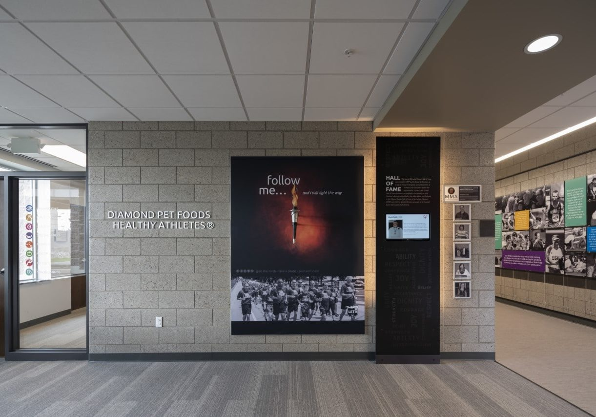 Interior photo of Training for Life Campus Healthy Athletes wing showing a sign with Diamond Pet Foods on the wall and a plastic LETR torch